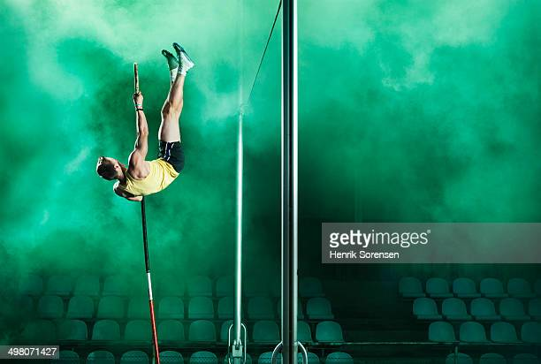 athlete jumping pole vault in smoke