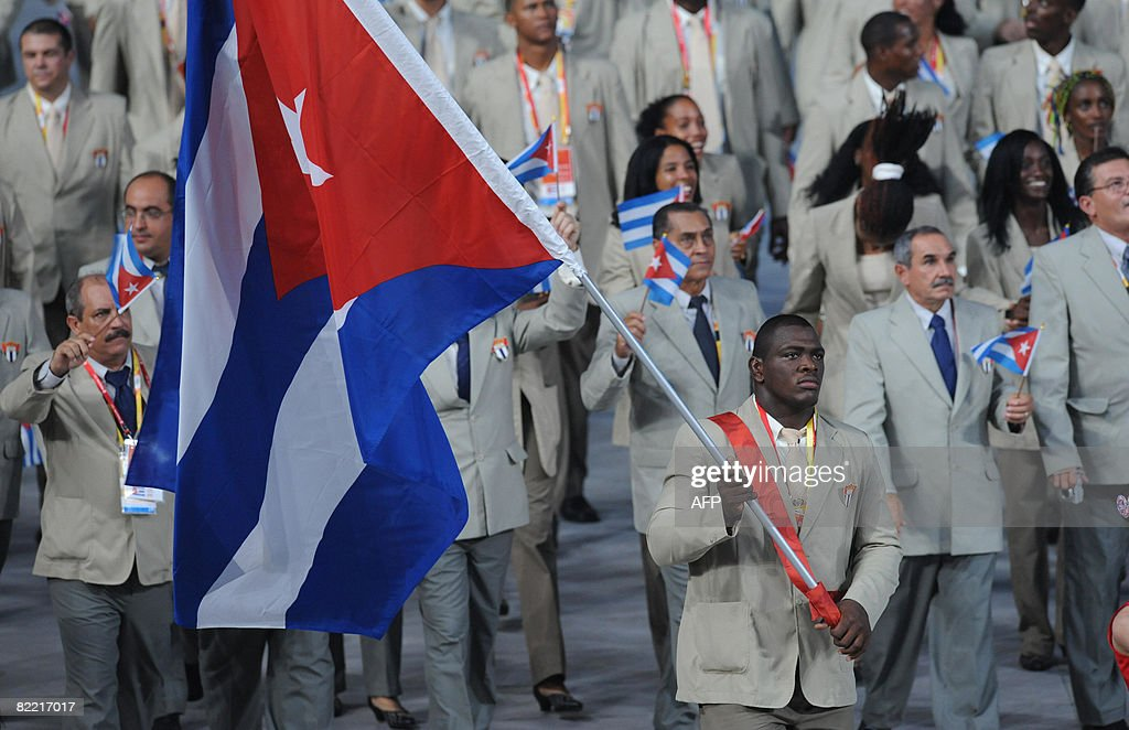 Athlete Mijain Lopez (C) Cuba's flag bearer parades in front of his delegation during the 2008 Beijing Olympic Games opening ceremony on August 8, 2008 at the National Stadium in Beijing. Over 10,000 athletes from some 200 countries are going to compete in 38 differents disciplines during the event, between August 9 to 24. AFP PHOTO / WILLIAM WEST