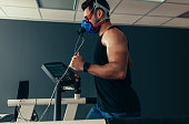 Sportsman with mask running on treadmill. Male athlete in sports science lab measuring his performance and oxygen consumption.