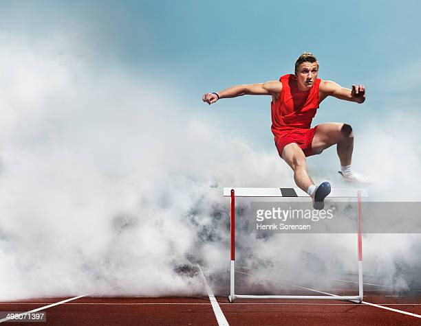 athlete over hurdle in smoke