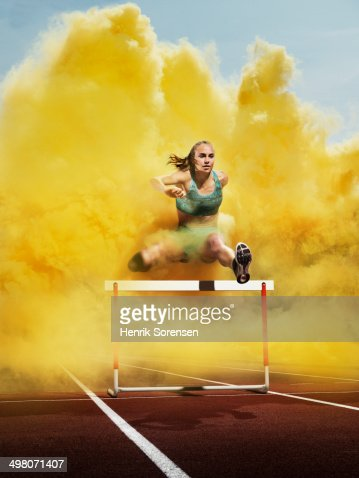athlete over hurdle in yellow smoke