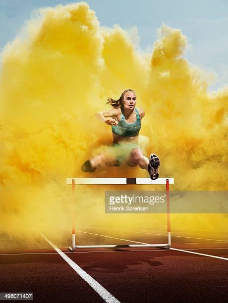 athlete over hurdle in yellow smoke