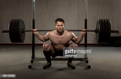 Athlete performing squat with barbell : Stock Photo