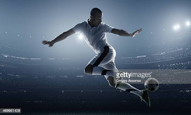 Athlete posed kicking a soccer ball in a stadium