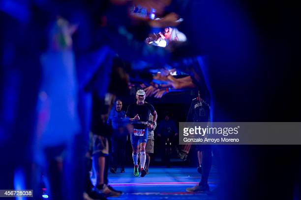 Athlete Robert Doussan is welcomed by a row of hands by Ironman staff as he arrives in last place at the finish line during the Ironman Barcelona on...