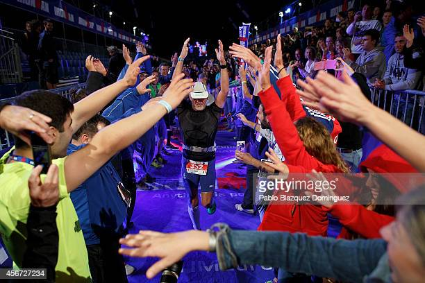Athlete Robert Doussan of France celebrates being the last competitor to cross the finish line of Ironman Barcelona on October 5 2014 in Calella city...