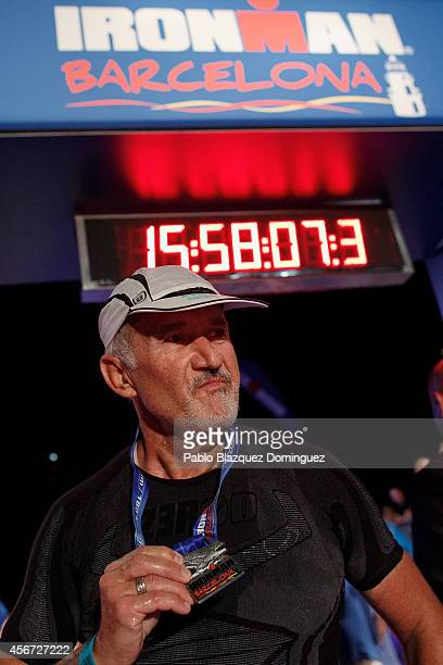 Athlete Robert Doussan of France holds his medal as he celebrates being the last competitor to cross the finish line of Ironman Barcelona on October...