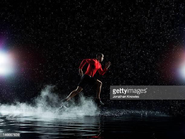 Athlete running in rain through water at night
