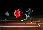 Athlete running on race track with parachute on back