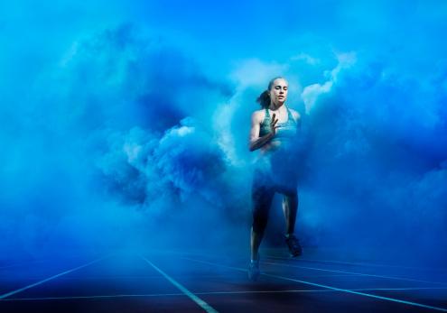 athlete running through blue smoke