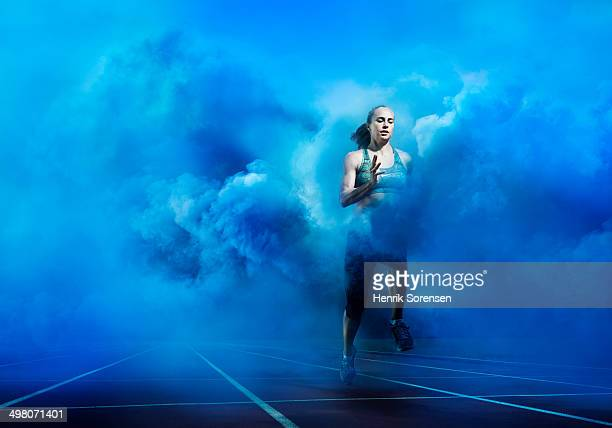 athlete running through blue smoke