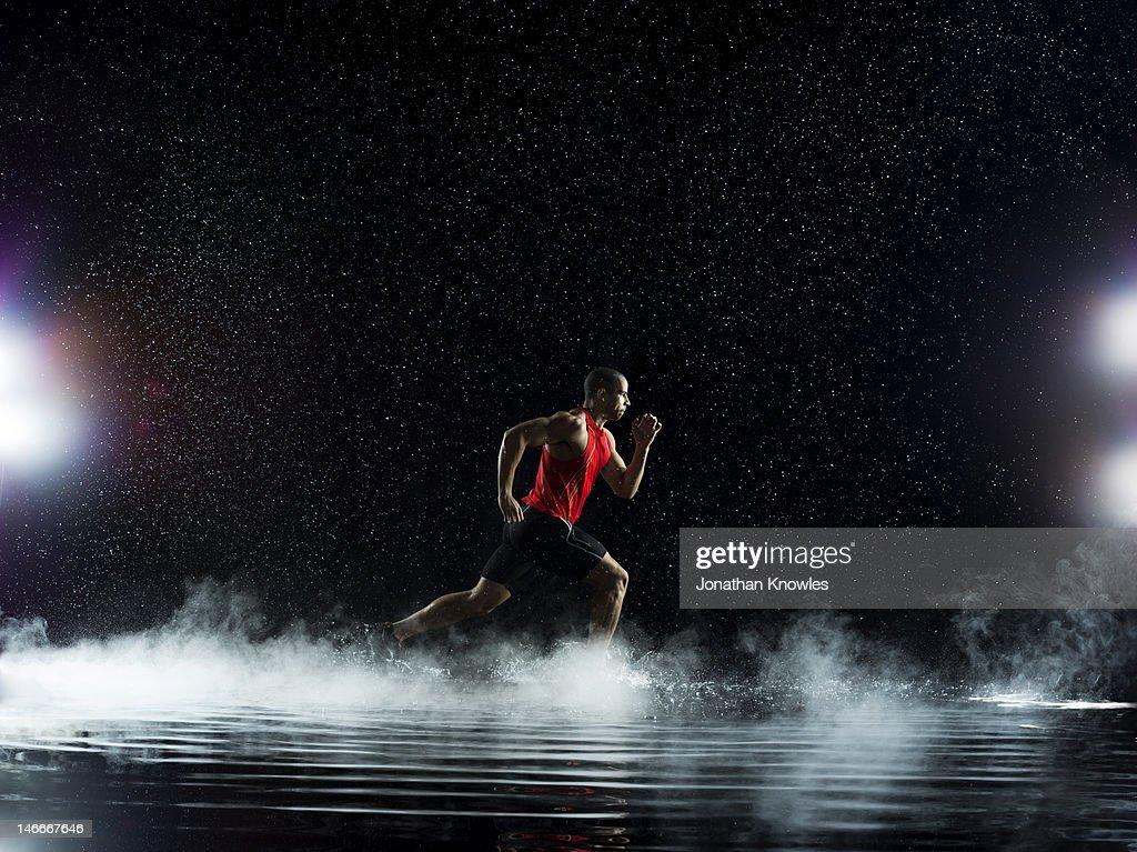 Athlete running through water, in rain at night : Stock Photo