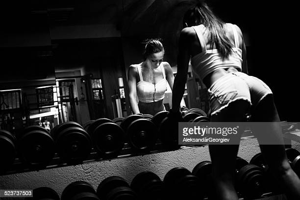 Athlete Sexy Women doing Dumbbell Exercise in Gym
