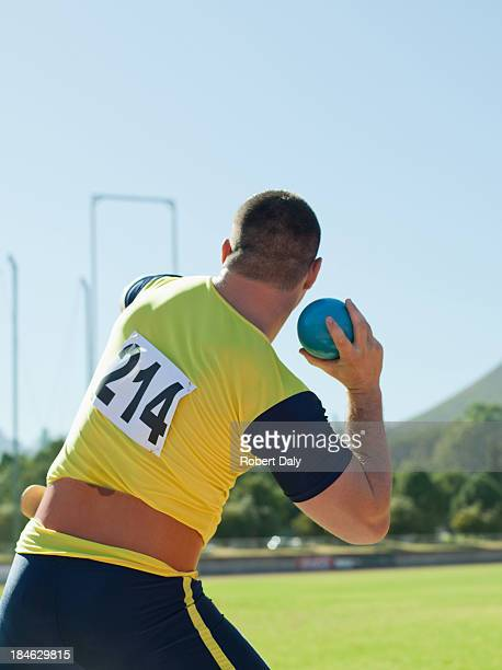 Athlete shot putting in an arena