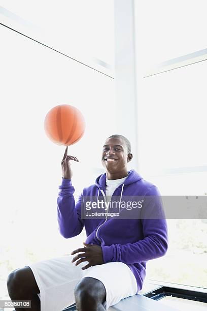 Athlete spinning basketball on finger