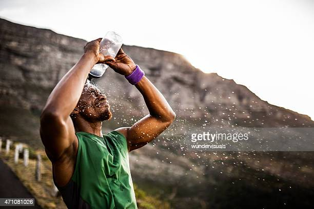Athlete splashing himself with water from his water bottle