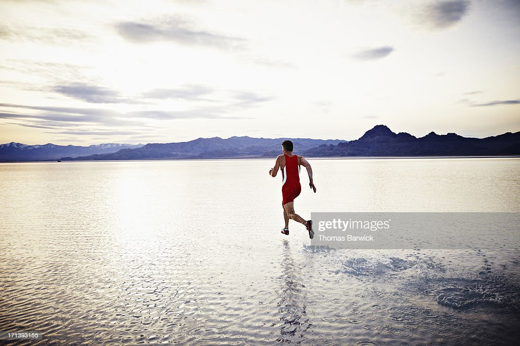 Athlete sprinting across surface of lake at sunset : Stock Photo