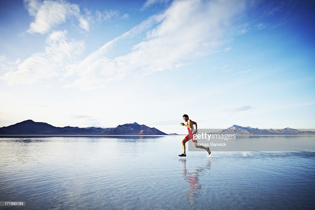 Athlete sprinting across surface of lake
