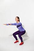 Athlete squatting in studio, smiling