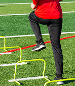 A high school athlete is performing speed and agility sports training drills stepping over yellow mini hurdles on a green turf field.