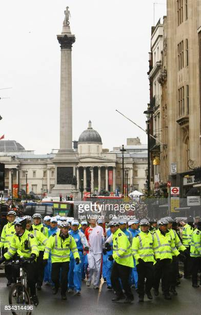 Athlete Steve Cram carries the Olympic torch during its relay journey across London on its way to the lighting of the Olympic cauldron at the O2...