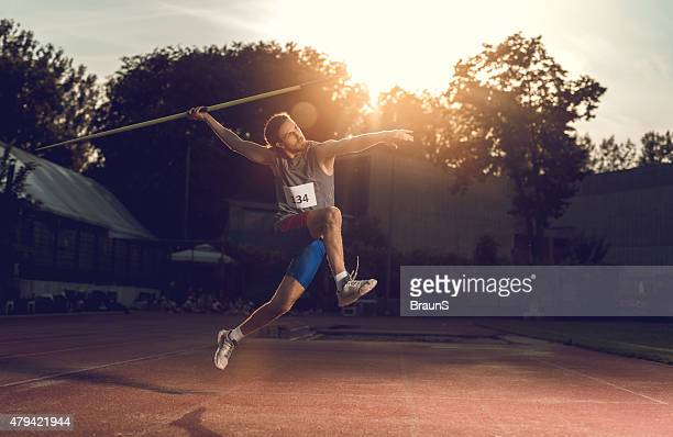 Athlete throwing a javelin on a stadium at sunset.
