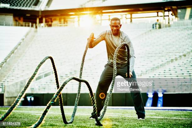 Athlete training with battle rope during workout