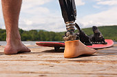 Athlete with an artificial leg and a waterski, on a dock