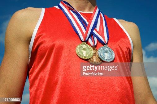 Sportler mit Gold Silber Bronze Medaillen strahlend blauem Himmel
