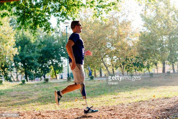 Athlete with prosthetic leg jogging in nature