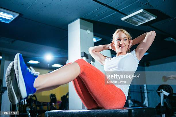 Athlete woman doing sit ups for abdominal muscles in gym