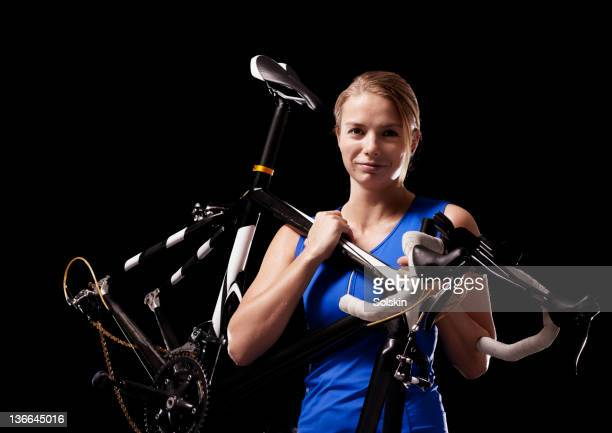 athlete woman holding cycle over shoulder