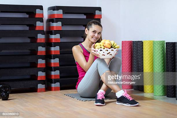 Athlete Woman Holding Fruit Basket on a Break in Gym.