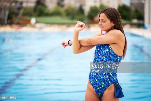 Athlete woman in swimwear near swimming pool