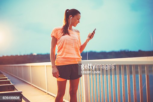 Athlete woman setting playlist to listen while jogging