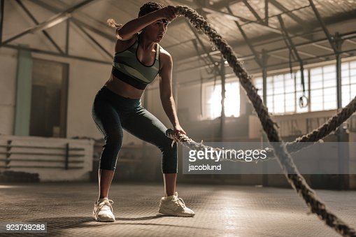 Athlete working out with battle ropes at cross gym : Foto de stock