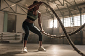Fitness woman using training ropes for exercise at gym. Athlete working out with battle ropes at cross gym.
