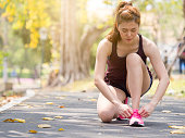 Athlete young woman sport runner tightening latching on running shoes/sneakers at track running stadium, sport running and fitness lifestyle concept