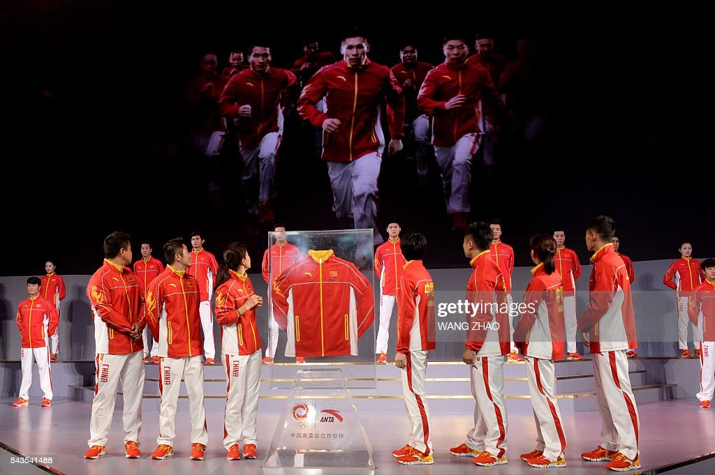 Athletes (front) and models parade during a ceremony to unveil the Chinese Olympic team's uniforms for the Rio 2016 Olympic Games, in Beijing on June 29, 2016. The uniforms were unveiled at a ceremony in the Water Cube, the venue for the swimming competition at the 2008 Beijing Olympic Games. / AFP / WANG