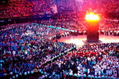 Athletes and spectators watch as flames rise from the Olympic cauldron during the opening ceremony for the London 2012 Olympic Games at the Olympic...