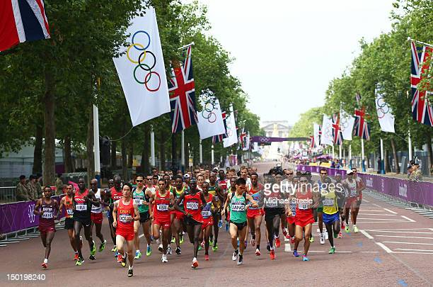 Athletes backdropped by the Queen Victoria Memorial and Buckingham Palace compete along the Mall in the Men's Marathon on Day 16 of the London 2012...