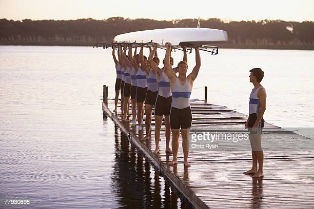 Athletes carrying a crew row boat over heads