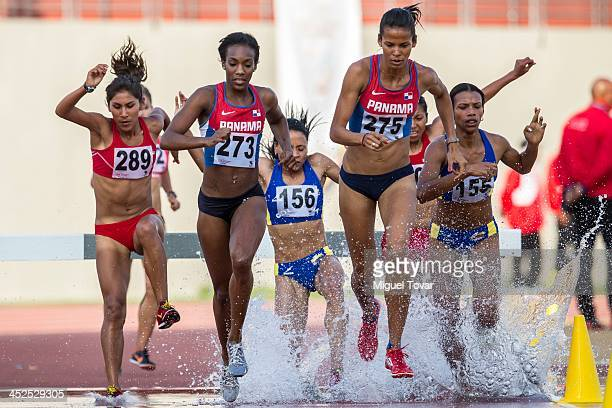 Athletes clear a water jump in the Women's 3000 metres steeplechase final as part of the XVII Bolivarian Games Trujillo 2013 at Chan Chan Stadium on...