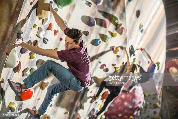 Athletes climbing rock wall in gym