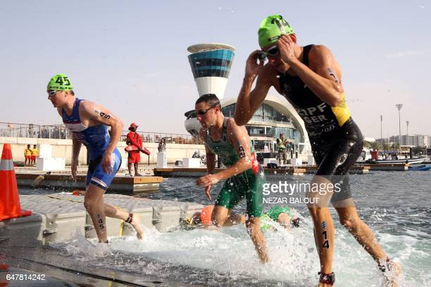 Athletes compete in the ITU World Triathlon at the Yas Marina Circuit in Abu Dhabi on March 4 2017 / AFP PHOTO / NEZAR BALOUT