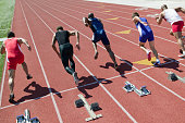 Male sprinters leaving starting blocks