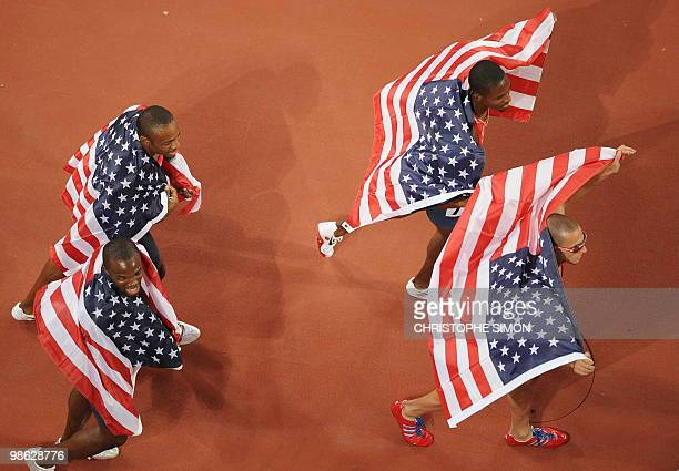 US athletes David Neville Lashawn Merritt Angelo Taylor and Jeremy Wariner wave their national flag as they celebrate winning gold in the men's...