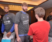 NBA athletes DeMarcus Cousins and Aaron Gray of The Sacramento Kings greet a student from The United Nations International School at an event...