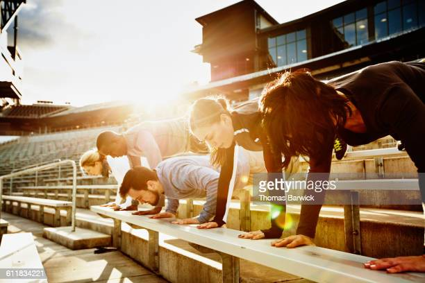 Athletes doing pushups on stadium bleachers