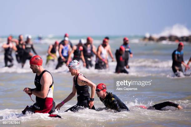 Athletes exit the water after completing the swim leg of Ironman 703 Italy race on June 18 2017 in Pescara Italy